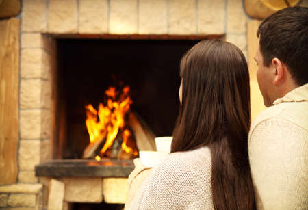 Couple holding cups with hot chocolate with marshmallows in front of lit fireplace photo