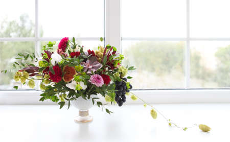 Unusual wedding composition with succulent flowers, grape, fig and hop in retro style near the window