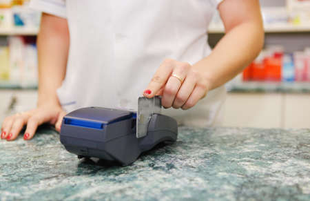 key card: Close up of human hand putting credit card into payment machine in drug store