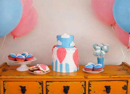 Elegant sweet table with big cake, cupcakes, cake pops on dinner or event party photo