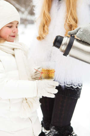 Happy young mother with daughter with water container on winter picnic photo