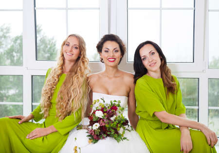 Cheerful bride with female friends holding bouquet indoors photo