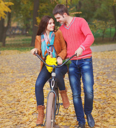 Happy young couple with bicycle in autumn park photo