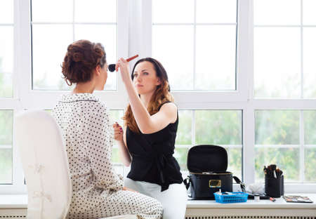 Make-up artist doing make up for young beautiful bride applying wedding make-up Reklamní fotografie