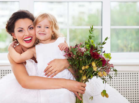 Smiling happy bride and a flower girl indoors. Horizontal shot photo