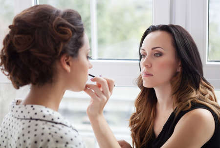 Make-up artist doing make up for young beautiful bride applying wedding make-up photo