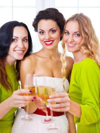 Happy bride and bridemaids holding wedding glass with champagne