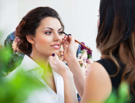 Make-up artist doing make up for young beautiful bride applying wedding make-up Stock Photo