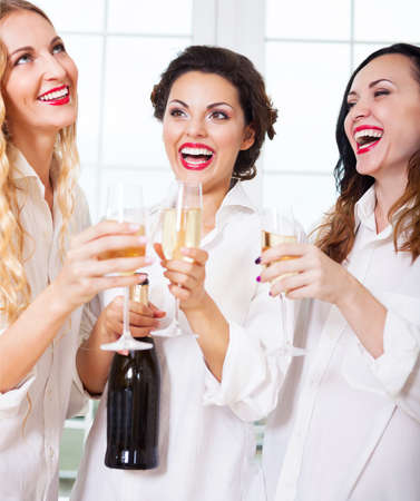 bridal couple: Bride to be and bridemaids holding glass with champagne wearing white