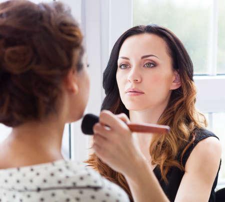 make up artist: Make-up artist doing make up for young beautiful bride applying wedding make-up Stock Photo