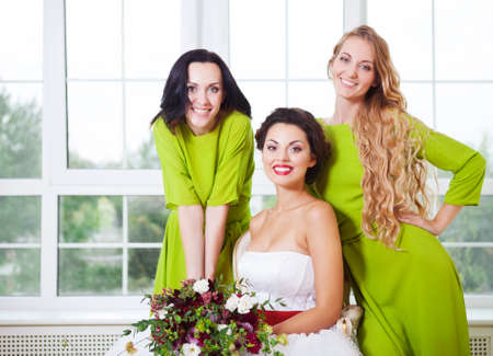 Cheerful bride with bridesmaid holding bouquet indoors photo