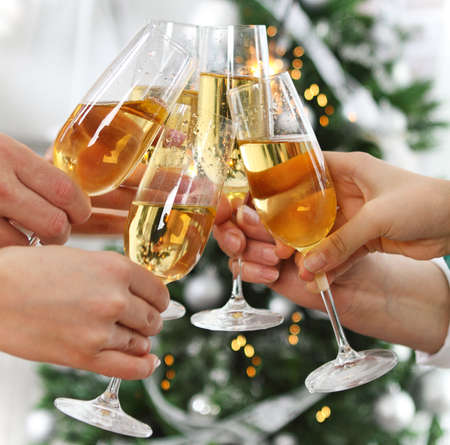 clinking: Christmas or New Year celebration. People holding glasses of champagne making a toast by the Christmas tree