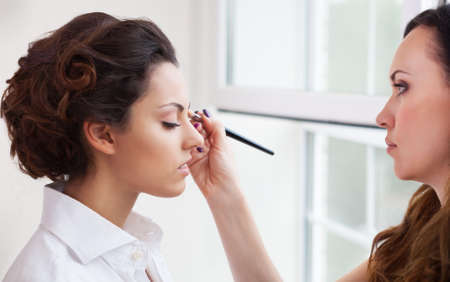 up service: Make-up artist doing make up for young beautiful bride applying wedding make-up Stock Photo