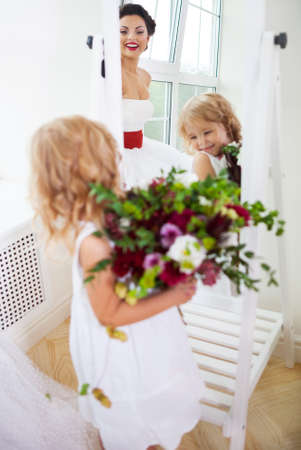 Smiling happy bride and a flower girl indoors. Vertical shot photo