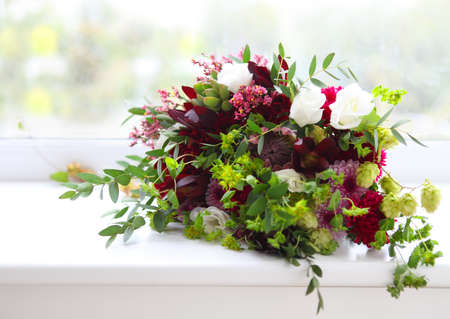 romantic flowers: Unusual wedding composition with succulent flowers, fig and hop in retro style near the window