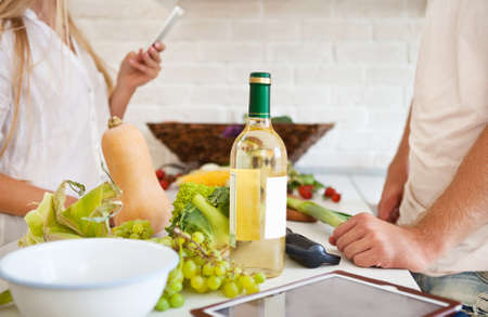 Happy young couple cutting vegetables at the kitchen. Couple preparing dining. Close up photo