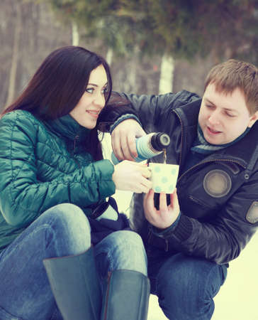 thermos: Happy young couple having fun in the winter park drinking hot tea