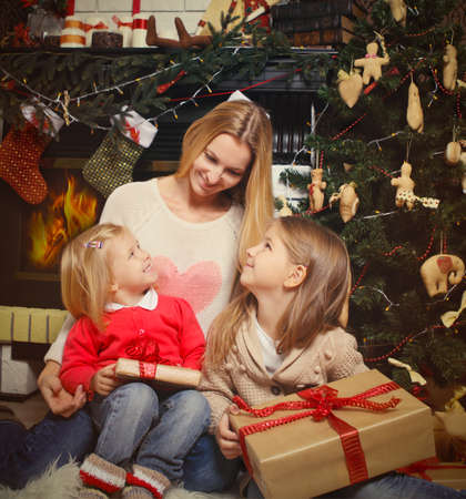 Young mother and her two little daughters with Christmas gifts by a Christmas tree in cozy living room with fireplace in winter photo