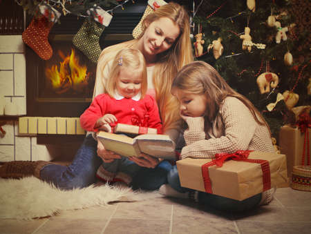 Young mother and her two little daughters with Christmas gifts reading the book by a Christmas tree in cozy living room with fireplace in winter photo