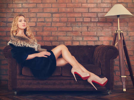 curved leg: Portrait of a beautiful woman in fur coat sitting on the sofa