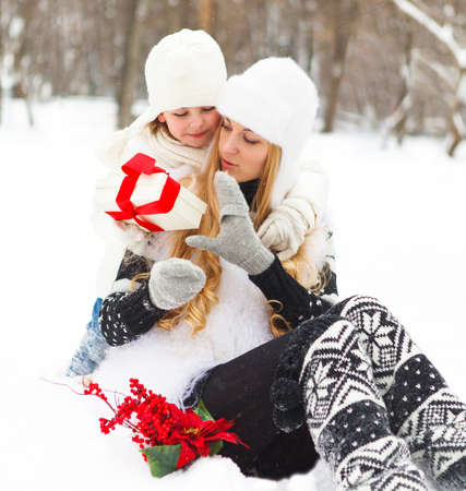 Happy young mother with daughter with present and christmas decorations on winter picnic photo