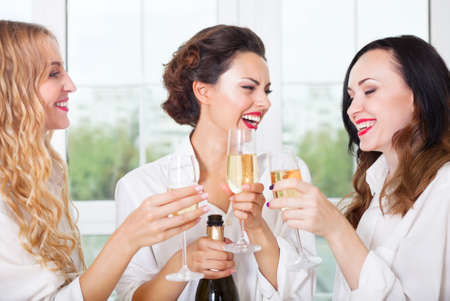 prewedding: Bride to be and bridemaids holding glass with champagne wearing white