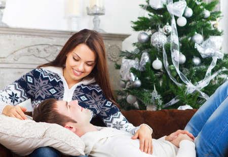 incendio casa: Feliz pareja joven que se sienta en el sofá por el árbol de Cristmas Foto de archivo