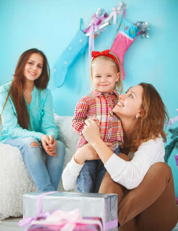 baby near christmas tree: Portrait of a mother with baby daughter and teen daughter being close and hugging at home near the Christmas tree being happy and joyful Stock Photo