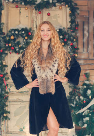 curved leg: Portrait of the beautiful happy woman in furcoat by the Christmas decorations