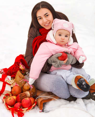 Young brunette mother with her daughter outdoors. Winter time photo