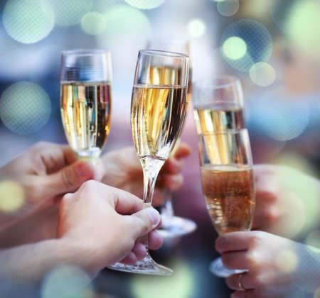 felicitaciones: Celebración. Las personas titulares de copas de champán haciendo un brindis