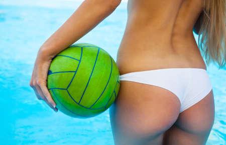 waterpolo: Vista trasera de la muchacha atractiva cerca de la piscina que sostiene la bola verde Foto de archivo