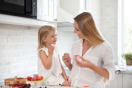 hand jam: Woman cooking homemade macarons at the kitchen with her little daughter Stock Photo