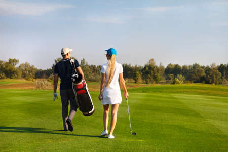 golf tournament: Young sportive couple playing golf on a golf course walking to the next hole Stock Photo