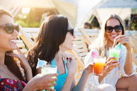 Glückliche Mädchen mit Getränken am Sommerfest der Nähe des Pools