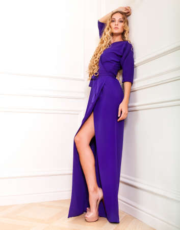 Portrait of the beautiful blond woman in long violet dress photo