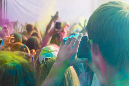 worshipers: Young man taking photo on mobile phone on holi color festival Stock Photo