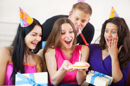 Portrait of joyful girl looking at birthday cake surrounded by friends at party photo