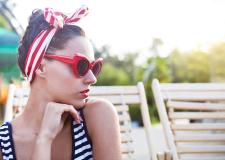 Beautiful pin up girl near the swimming pool. Summertime photo