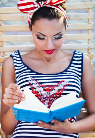 Beautiful pin up girl reading the book near the swimming pool. Summertime photo