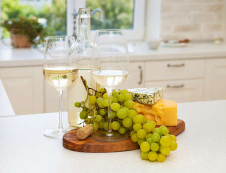 Various sorts of cheese, grapes and two glasses of the white wine at the white clean cozy kitchen