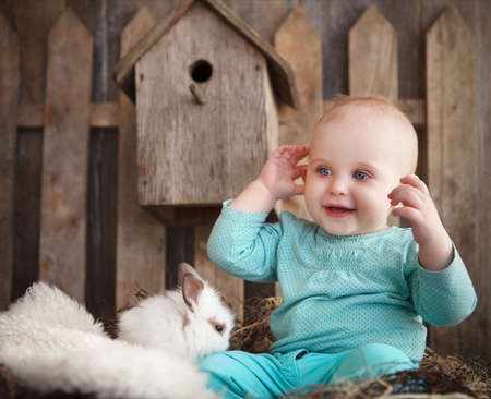 Portrait of an adorable baby girl and little white rabbit near the wooden background. Easter concept photo