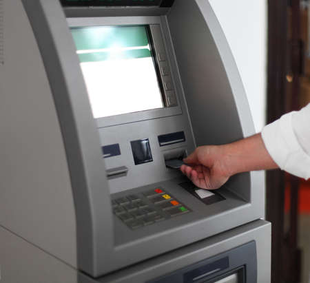 atm: Close up of hand of a man using banking machine Stock Photo