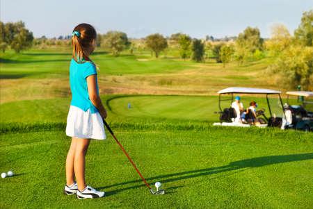 Niña linda que juega al golf en un campo al aire libre. Verano Foto de archivo - 35327963