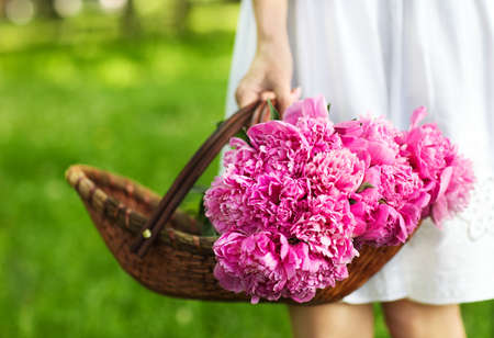 Woman holding basket of peony in her hand. Close up