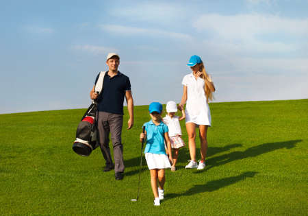 golf clubs: Family of golf players walking  at the course