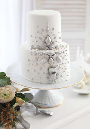White wedding cake with silver decoration and wedding bouquet with ranunculus
