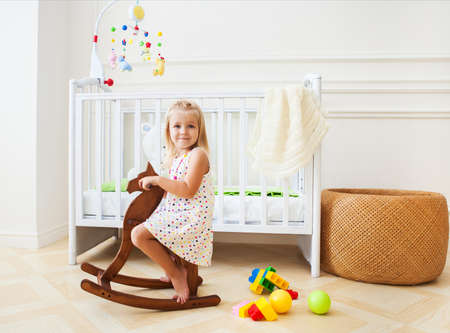Little cute girl in nursery room with basket, toys and wooden horse