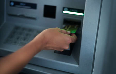 automatic teller machine bank: Close up of hand of a woman using banking machine