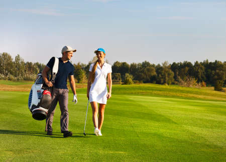 Young sportive couple playing golf on a golf course walking to the next hole Archivio Fotografico